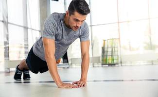 man doet push-ups in de sportschool foto