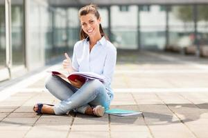 brunette vrouwelijke student zittend op de vloer met laptop foto