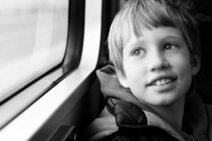 schattige jongen kijkt door het raam foto