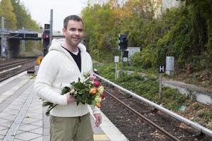 man te wachten op treinstation met bloemen foto