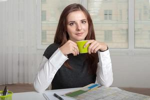 meisje met een kopje groen in de buurt van zijn mond foto