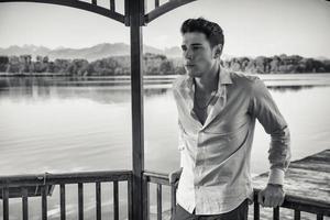 knappe jonge man op een meer in zonnige, rustige dag foto