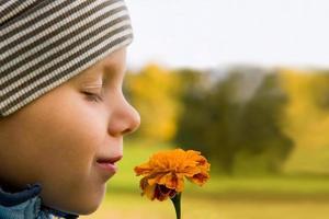 jongen ruikende bloem foto
