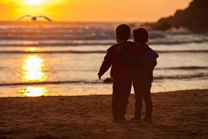 prachtige foto van twee jongens op het strand bij zonsondergang