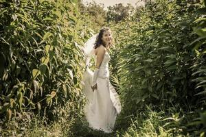 gelukkige mooie bruid die zich in gras en smilling bevindt. foto