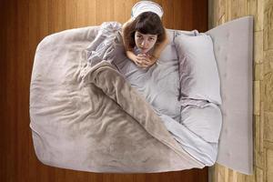 bovenaanzicht van jonge vrouw bidden in de slaapkamer