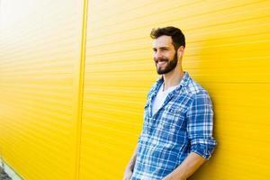 jonge knappe man met koptelefoon op gele muur foto