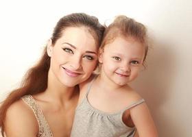 mooie glimlachende moeder en kleine gelukkige dochter knuffelen. foto