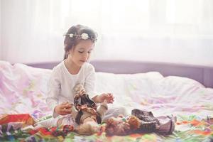 schattig klein meisje, spelen met poppen in bed thuis foto