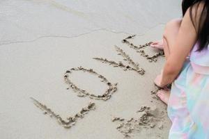 """gelukkige jonge vrouw op het strand dat """"liefde"""" woord schrijft foto"""