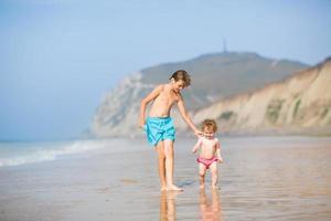 twee kinderen, broer en zusje, rennen op het prachtige strand foto