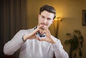 knappe jonge man hart ondertekenen met zijn handen maken foto