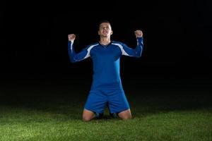 voetballer viert de overwinning op zwarte achtergrond foto