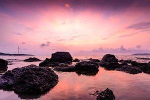 zeegezicht met steen bij zonsopgang. foto