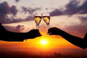 glazen met champers bij zonsondergang foto