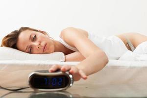 slaperige langharige vrouw wordt wakker in haar bed foto
