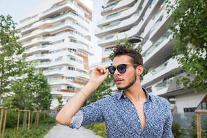 jonge knappe man poseren in de straten van de stad foto
