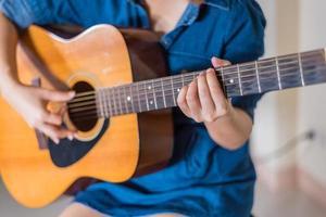 het meisje dat akoestische gitaar speelt isoleert op wit foto