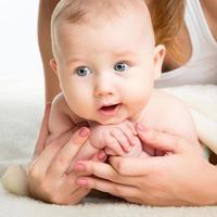 portret van een schattige baby in de zorgzame handen van een moeder. foto