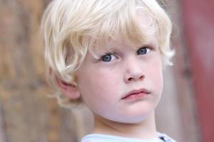 blonde kleine jongen met blauwe ogen, serieuze blik. foto
