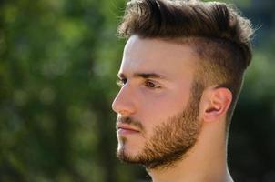 portret van knappe jonge man buiten in de natuur foto