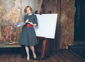 mooie vrouw kunstenaar met een leeg canvas en borstels foto