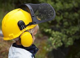 kleine blonde jongen in beschermende helm met vizier en oorbeschermers