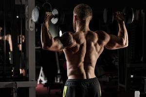 sterke en knappe jonge man doen oefening met halters foto