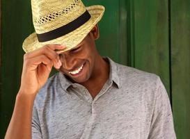 gelukkig jonge man met hoed lachen en naar beneden te kijken