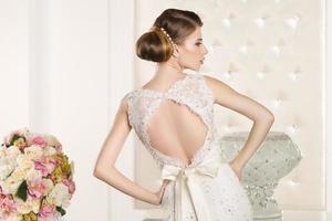 prachtige bruid in een witte kamer foto