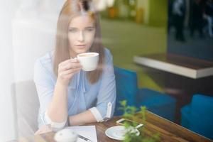 ernstige vrouw in de coffeeshop cappuccino drinken foto