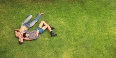 hou van jonge mooie mode paar liggend op groen gras achtergrond foto