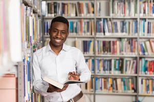 gelukkig mannelijke student met boek in bibliotheek foto