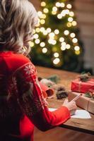 blonde vrouw die op Kerstmisprentbriefkaar schrijft foto