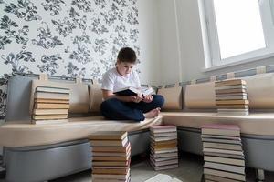 tienerjongen die een boek in ruimte leest foto