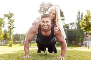 man doet push-ups met vrouw achterop foto