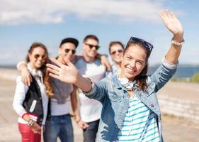 tienermeisje met een koptelefoon en vrienden buiten foto