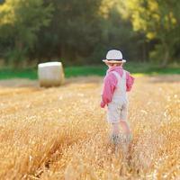 grappige kleine jongen-jongen in lederen korte broek lopen tarweveld foto