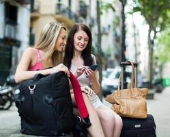 twee vriendinnen met bagage met behulp van de kaart foto