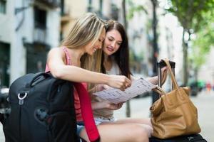 twee lachende meisjes met kaart foto