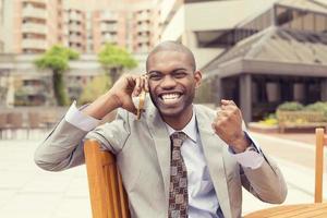 succesvolle man praten op mobiele telefoon ontvangt goed nieuws foto