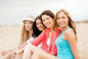 lachende meisjes met drankjes op het strand foto
