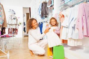 klein lachend meisje met mooie moeder winkelen foto