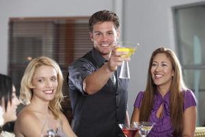 vrienden roosteren aan een bar foto