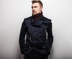 elegante jonge knappe man in zwarte jas. studio mode portret.