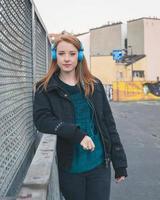 mooi meisje met koptelefoon poseren in de straten van de stad foto