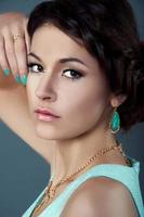 studioportret van mooie brunette in blauwgroen kleding
