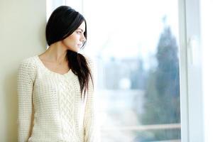 jonge mooie vrouw die venster bekijkt
