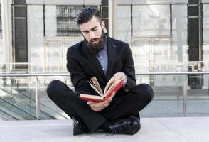jonge hipster lezen van een boek buiten zitten foto