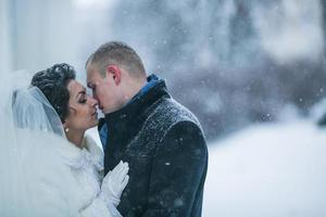 bruid en bruidegom wandelen in de sneeuw foto